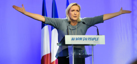"TOPSHOT - French far-right Front National (FN) party's President, Marine Le Pen, gestures as she delivers a speech on stage during the FN's summer congress in Frejus, southern France, on September 18, 2016.  Marine Le Pen's slogan reading ""In the name of the [French] people"" is seen on the rostrum. / AFP / Franck PENNANT        (Photo credit should read FRANCK PENNANT/AFP/Getty Images)"