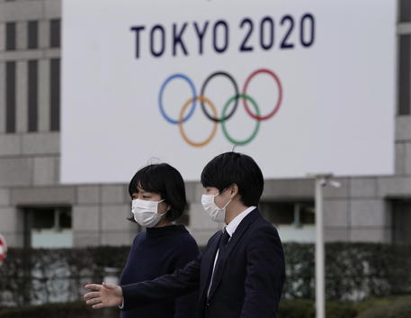 epa08254724 Pedestrians wearing masks walk past the emblem of the Tokyo 2020 Olympic Games displayed on a wall of Tokyo Metropolitan Government headquarters in Tokyo, Japan, 28 February 2020. Organizers of the 2020 tokyo Olympics stated that planning for the games, scheduled to begin 24 July, is going ahead as scheduled. Recently, a member of the International Olympic Committee (IOC) inferred that organizers would have until late May to make a decision in regards to whether to postpone the games, yet this deadline and general statement has been disputed by the Tokyo Organizing Committee and other members of the IOC. There have been concerns that the games will be affected by the novel coronavirus and COVID-19 outbreak. EPA/KIMIMASA MAYAMA