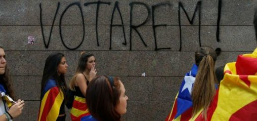 """Students wear Esteladas (Catalan separatist flag) during a demonstration in favor of the banned October 1 independence referendum in Barcelona, Spain September 28, 2017. The graffiti on the wall reads, """"We will vote!"""". REUTERS/Jon Nazca"""